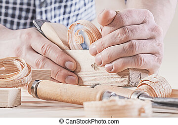 woodworkers plane in hands of carpenter very close up