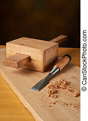 Woodworking tool. Mallet with chisel and savings on workbench.