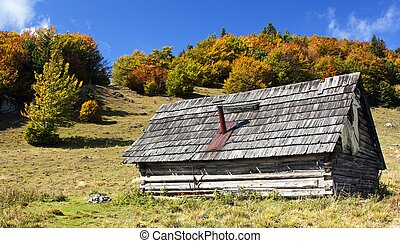 woody chalet on the mountains with sky and clouds