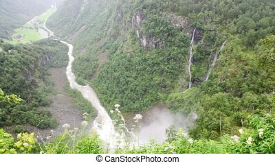 mountains with falls, fiord and small houses in valley below