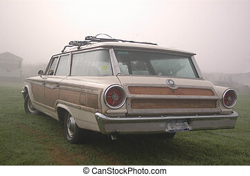 a classic woody type station wagon from the 70s in the morning mist by the sea