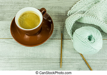 Wool ball with a cup of coffee and needles