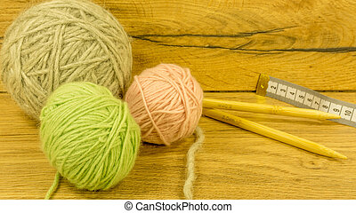 Wool ball with knitting needles on a wooden ground
