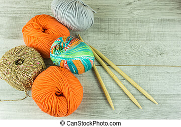 Wool balls in different colors with knitting needles on a wooden table