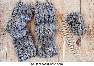wool grey legwarmers, knitting needles and yarn on wooden...