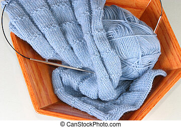 Blue wool knitting yarn and knitting project in a hand-made pecan wooden bowl with circular knitting needles.