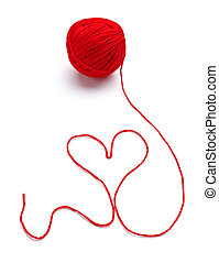 close up of a wool ball and heart shape on white background
