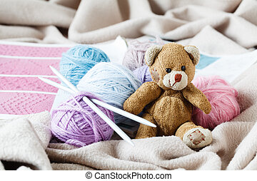 Wool yarn in coils with knitting needles on light background