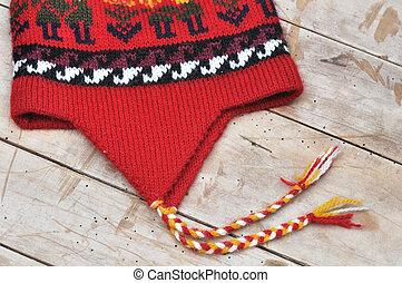 woolen cap - red peruvian cap on wooden board