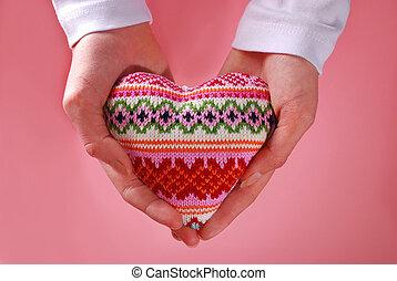 woolen heart in hands - woolen heart holded in hands on pink...