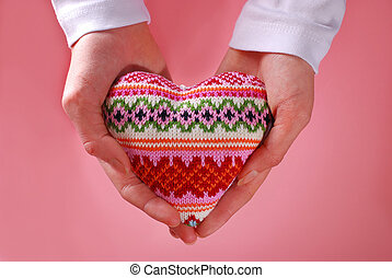 woolen heart holded in hands on pink background