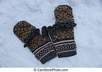 woolen mittens are lying on the snow