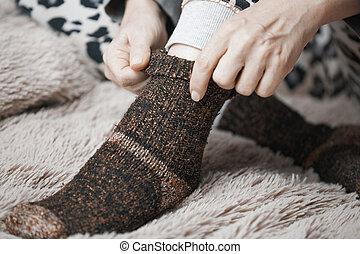 Woman hands putting on warm woolen socks