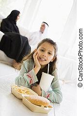 woonkamer, key/selective, voedingsmiddelen, (high, jonge, vasten, ouders, achtergrond, focus), het glimlachen van het meisje