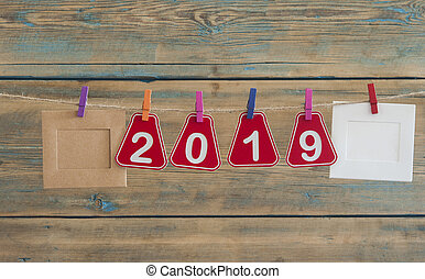 word 2019 and photo frame hanging on a rope over wooden background.