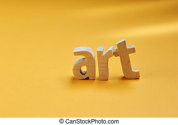 Word ART carved from wood stand on yellow backdrop for your desing, Art text