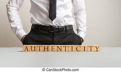 Word Authenticity spelled on desk with wooden cubes