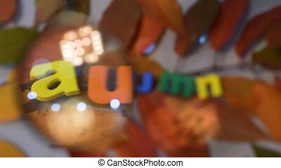 Word autumn of colorful letters through magnifying glass on...