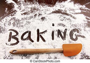 Word baking written in white flour on wooden table