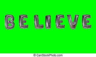 Word believe from helium silver balloon letters floating on...
