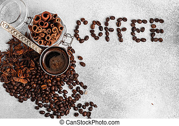 Word coffee made of roasted beans with copper turk and cinnamon sticks on light coloured surface