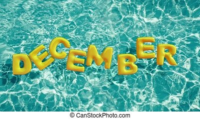 "word ""DECEMBER"" shaped inflatable swim ring floating in a..."