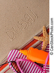 Word DUBAI written in sand with beach accessories.