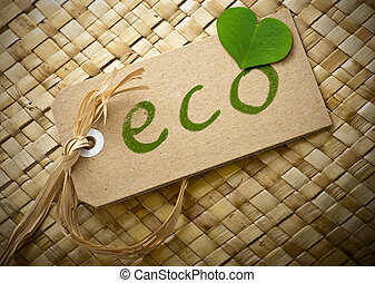 word eco written onto a carboard label and raffia string, brown background