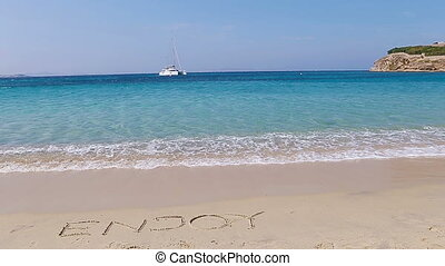 Word Enjoy handwritten on sandy beach with soft ocean wave on background. Idea for advertising