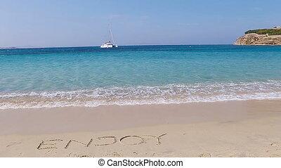 Word Enjoy handwritten on sandy beach with soft ocean wave on background. Idea for advertising