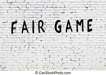 Word fair game painted on white brick wall