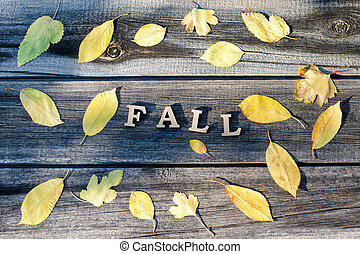 Word Fall on a wooden background, frame of yellow leaves