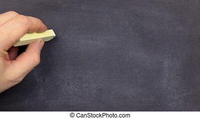 Word FASHION, written by hand in chalk on a blackboard. Hand...