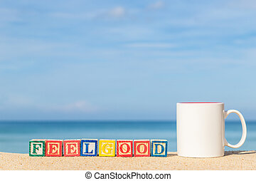 word FEELGOOD in colorful alphabet blocks on tropical beach