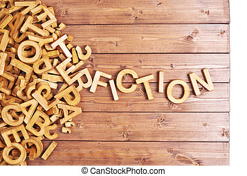 Word fiction made with block wooden letters next to a pile of other letters over the wooden board surface composition