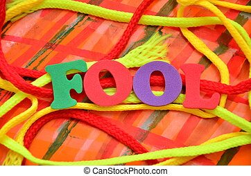 word fool on an abstract colored background