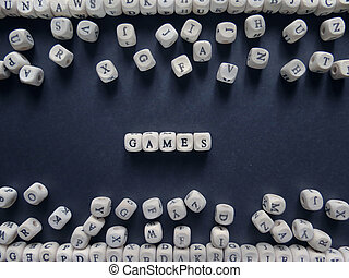 Word Games of small white cubes next to a bunch of other letters on the surface of the composition on a dark background
