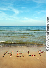 Word HELP on beach sand, made from rocks