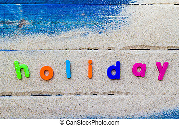 word holiday laid sand blue board