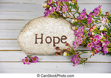 word hope on stone with flowers