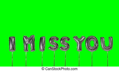 Word I miss you from helium silver balloon letters floating...