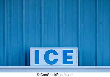 Word ICE in capital letters on sign in front of cold blue metal wall
