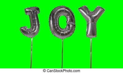 Word joy from helium silver balloon letters floating on...