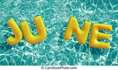 "word ""JUNE"" shaped inflatable swim ring floating in a..."