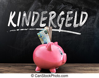 word KINDERGELD, German for child benefit, on blackboard with piggy bank and cash in front on wooden table