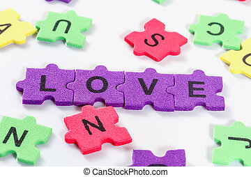 word LOVE formed with colorful foam puzzle on white background