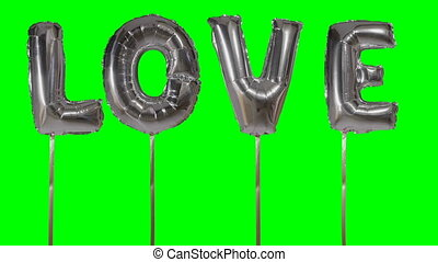 Word love from helium silver balloon letters floating on green screen
