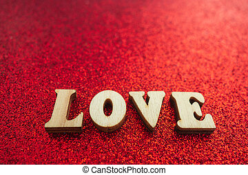 Word love in wooden letters on a bright red shiny background. Happy Valentine's Day, Mother's Day, March 8, World Women's Day holiday card concept.