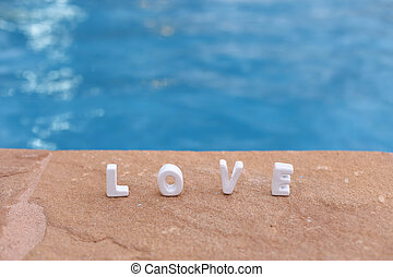 word Love on the rock and water