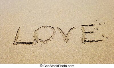 Word love on the sand that wiped off by sea wave. 4K...